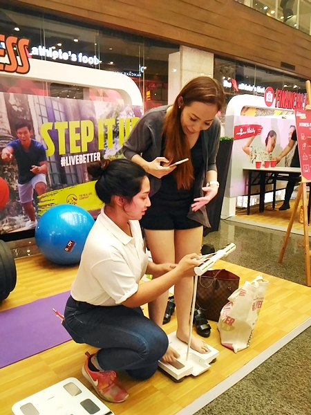 Blogger tries one of the activity booths and measured weight and body fat.